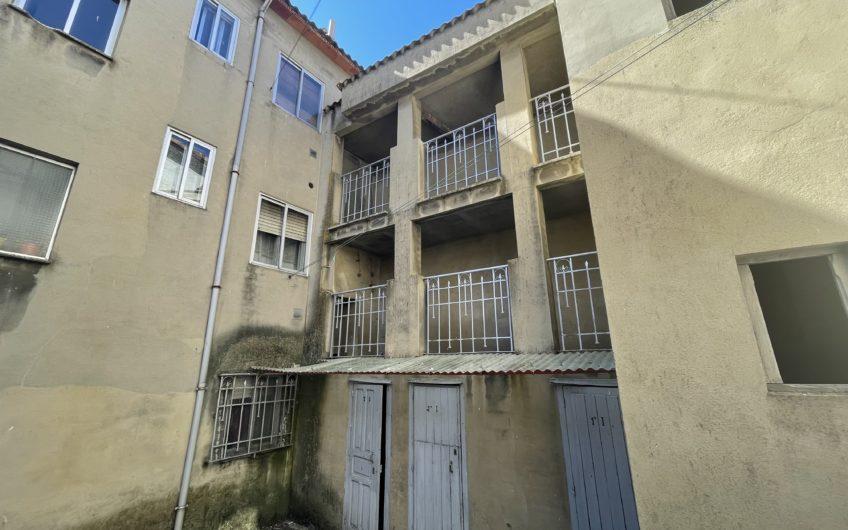 Edificio con trasteros y casa de fachada de piedra anexa en Villamanin